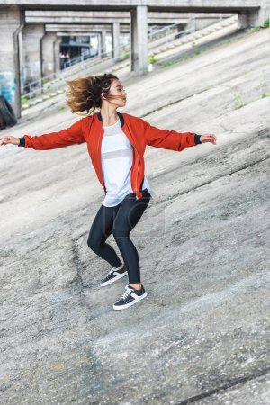 young asian stylish female urban dancer dancing at city street