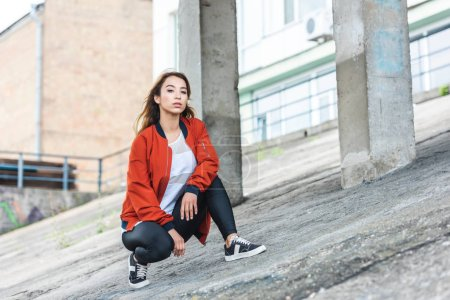 confident stylish asian woman sitting and looking at camera at urban street