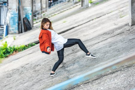 Photo for Young asian stylish female urban dancer dancing at city street - Royalty Free Image