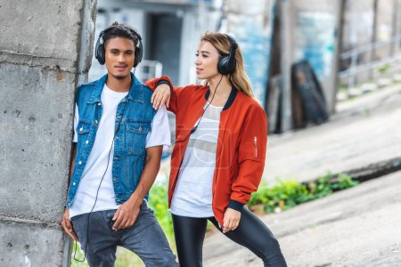 stylish multicultural couple with headphones standing at city street