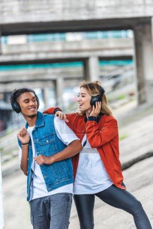 Foto de Feliz pareja multicultural escuchando música con auriculares y bailando en la calle de la ciudad - Imagen libre de derechos