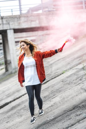 stylish young asian woman holding red smoke bomb at city street