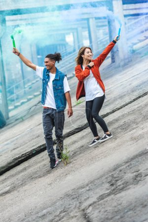 young multicultural couple holding colorful smoke bombs at city street