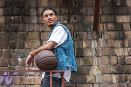 stylish mixed race man standing with basketball ball and looking away at street