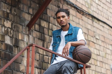 young mixed race man standing with basketball ball and looking at camera at street