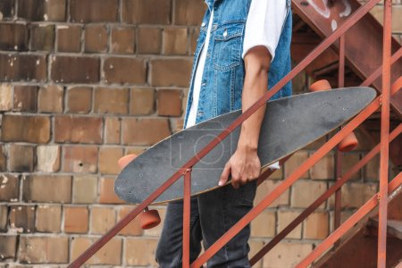Photo for Cropped image of stylish man holding skateboard at urban street - Royalty Free Image