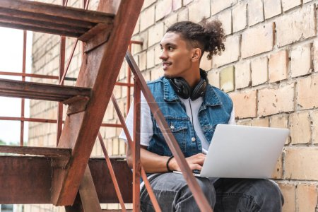 Photo for Focused mixed race male freelancer in headphones working with laptop and looking away at street - Royalty Free Image