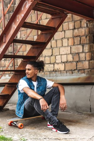 Photo for Stylish mixed race man sitting on skateboard at urban street - Royalty Free Image