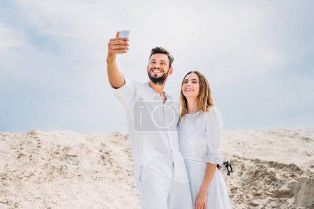 heureux jeune couple en vêtements blancs prenant selfie dans le désert