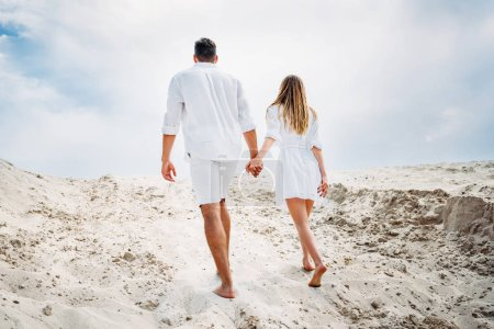 Photo pour Vue arrière du jeune couple en vêtements blancs marcher par le sable pieds nus - image libre de droit