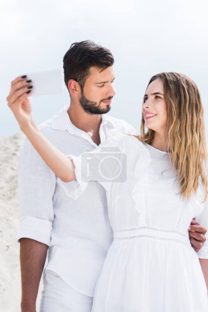loving young couple in white clothes taking selfie in desert