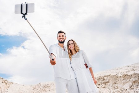 happy young couple taking selfie with monopod and smartphone in desert
