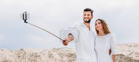 smiling young couple taking selfie with monopod and smartphone in desert
