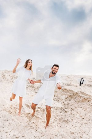 playful young couple taking selfie with monopod and smartphone in desert