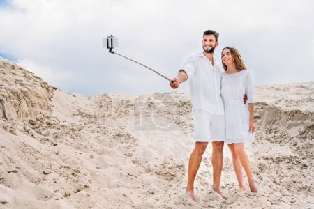 beautiful young couple in white clothes taking selfie with monopod and smartphone in desert