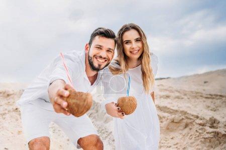 Photo pour Heureux jeune couple en blanc avec des cocktails de noix de coco en regardant caméra - image libre de droit