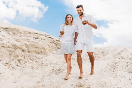 happy young couple in white with coconut cocktails walking on sandy dunes