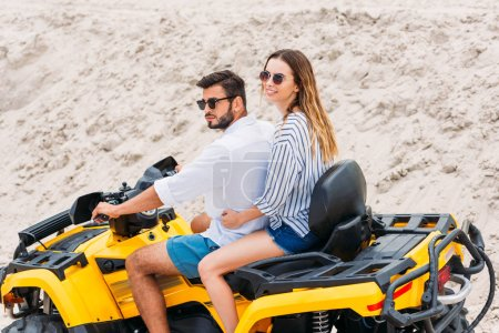 beautiful young couple in sunglasses riding all-terrain vehicle in desert