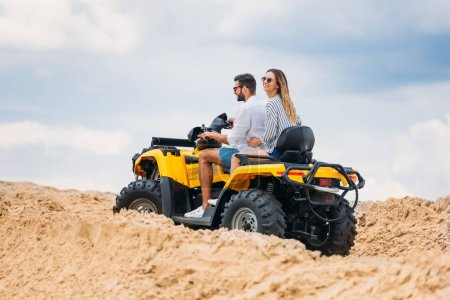 active young couple riding all-terrain vehicle in desert on cloudy day
