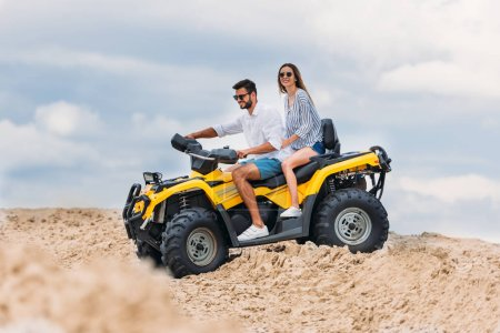 happy young couple riding all-terrain vehicle in desert on cloudy day