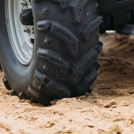 cropped shot of wheel of all-terrain vehicle on sand