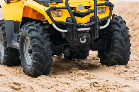 partial view of all-terrain vehicle on sand