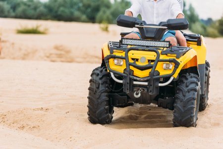 cropped shot of couple riding all-terrain vehicle on sand