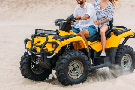 cropped shot of active young couple riding all-terrain vehicle in desert