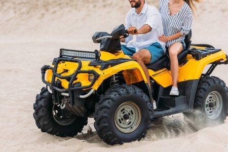 Photo pour Recadrée tir d'active jeune couple riding véhicule tout-terrain dans le désert - image libre de droit