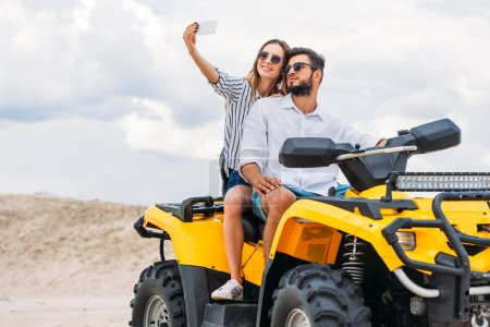 attractive young couple taking selfie while sitting on ATV in desert