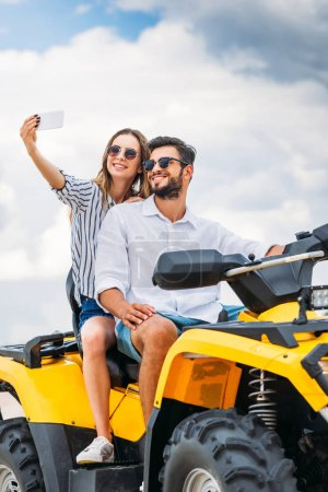 smiling young couple taking selfie while sitting on ATV