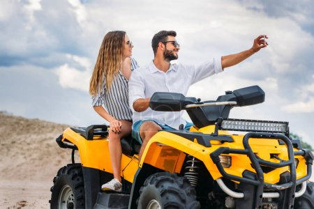 active young couple taking selfie while sitting on ATV in desert