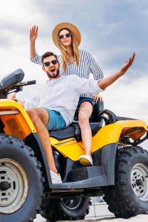 happy young couple sitting on ATV in front of cloudy sky and looking at camera