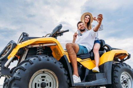 Photo pour Heureux jeune couple assis sur VTT et prendre selfie - image libre de droit
