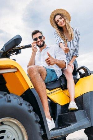 feliz joven pareja sentado en ATV y mostrando los pulgares hacia arriba