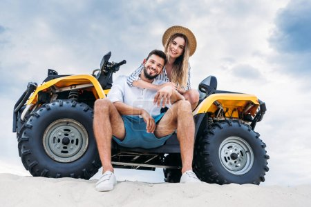 bottom view of happy young couple sitting on ATV on sandy dune in front of cloudy sky