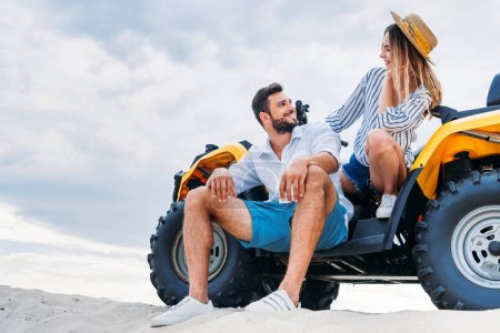 Photo for Happy young couple sitting on ATV on sandy dune in front of cloudy sky - Royalty Free Image