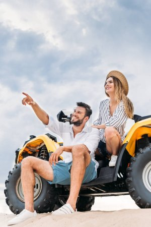 beautiful young couple sitting on ATV on sandy dune and pointing somewhere