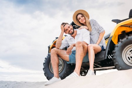 Photo for Beautiful young couple sitting on ATV on sandy dune and looking at camera - Royalty Free Image