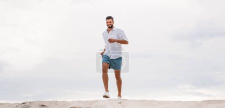 handsome young man running on sand dune in front of cloudy sky