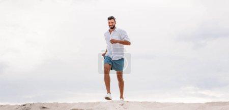 beau jeune homme s'exécutant sur une dune de sable en face de ciel nuageux