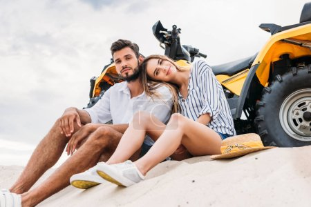 bottom view of beautiful young couple sitting near ATV on sandy dune and looking at camera