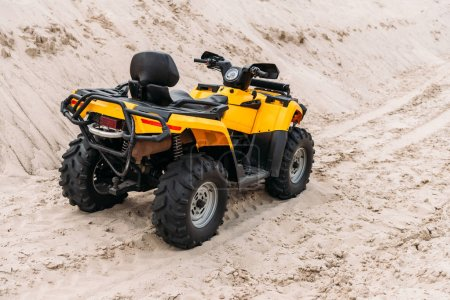 yellow all-terrain vehicle parked on sand