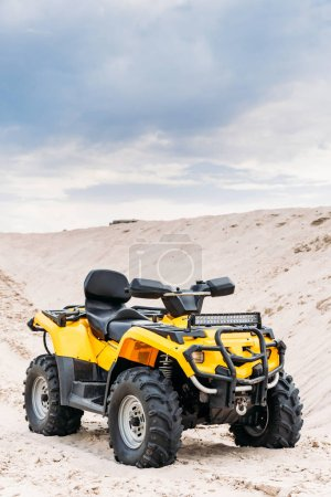 Photo for Modern yellow all-terrain vehicle standing in desert on cloudy day - Royalty Free Image