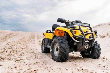bottom view of modern yellow all-terrain vehicle standing in desert on cloudy day