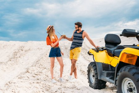 relaxed young couple with atv and coconut cocktails in desert