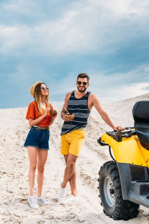 smiling young couple with atv and coconut cocktails in desert