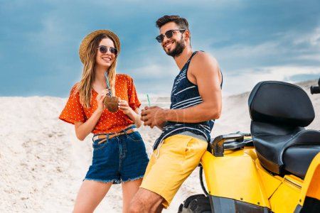 happy young couple with atv and coconut cocktails in desert