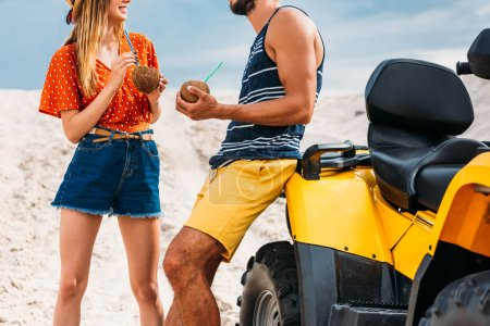 cropped shot of young couple with atv and coconut cocktails in desert