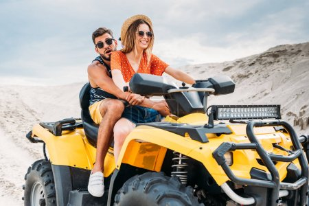 beautiful young couple riding all-terrain vehicle in desert on cloudy day